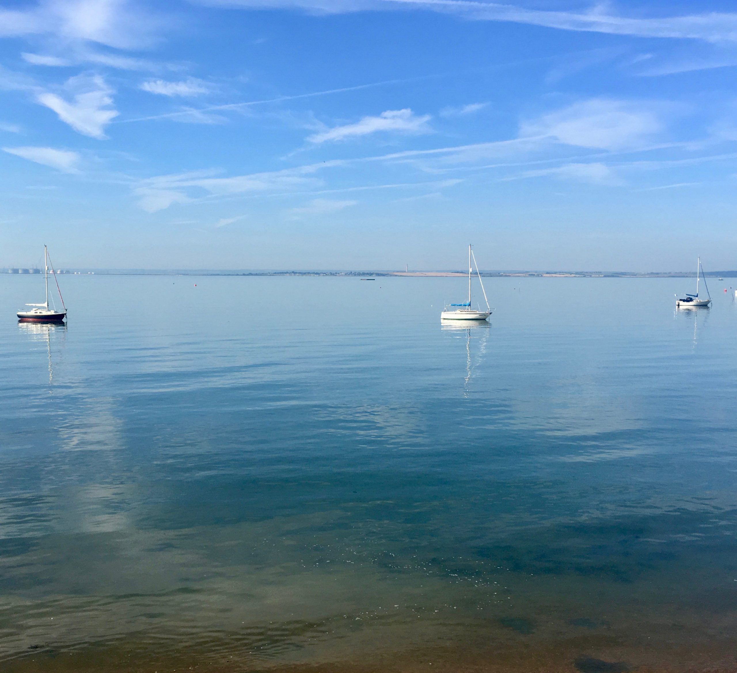 A blue sky, with three boats upon a peaceful and still sea scape